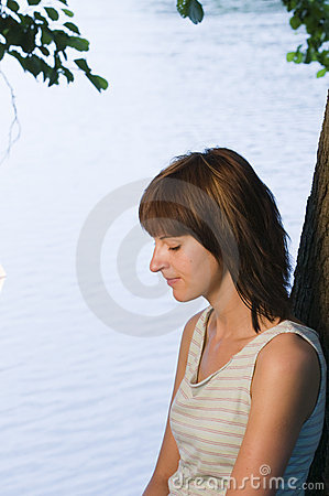 Thoughtful woman by lake