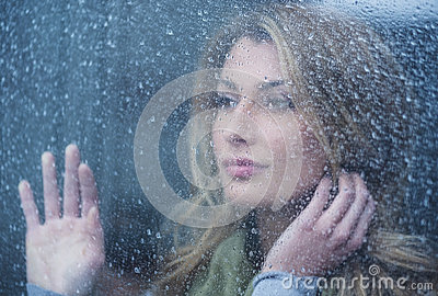 Thoughtful Woman Looking Through Window With Raindrops