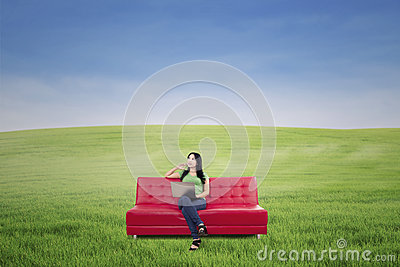 Thoughtful woman on red sofa at green field