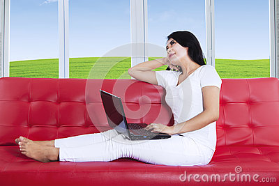 Thoughtful woman using laptop at home