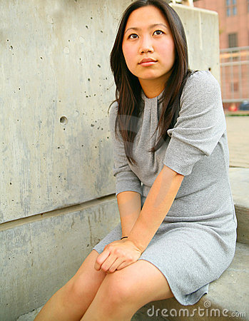 Thoughtful Young Asian Girl Sit Outdoor
