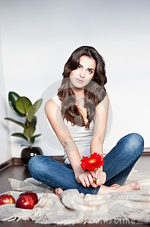 Thoughtful young casual female with red flower