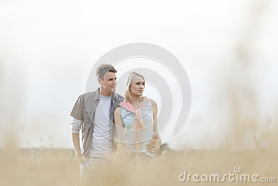 Thoughtful young couple looking away while standing at field