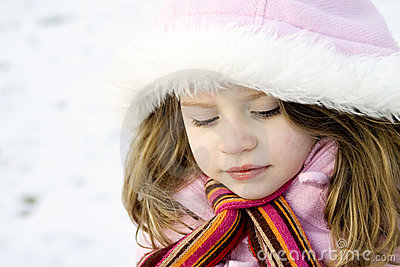 Thoughtful young girl with parka in the snow