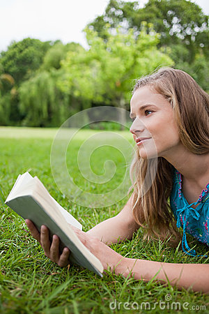 Thoughtful young woman holding a book
