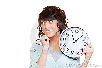Thoughtful young woman holding clock