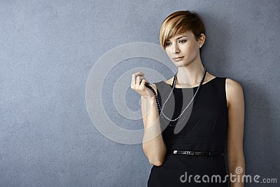 Thoughtful young woman looking at pearl necklace