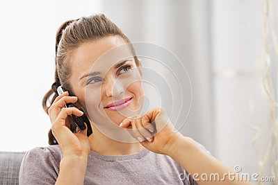 Thoughtful young woman sitting on couch and talking mobile phone