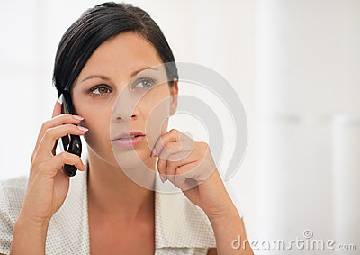 Thoughtful young woman speaking mobile phone