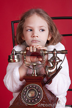 Thougtful little girl with old phone