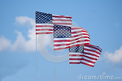 Three American Flags Waving in Clouds