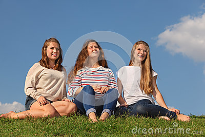 Three barefoot girls sit and look into distance