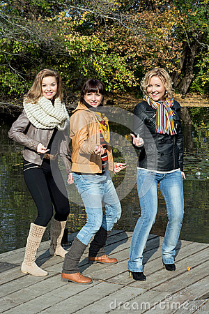 Three beautiful joyful woman posing on a pier at the lake