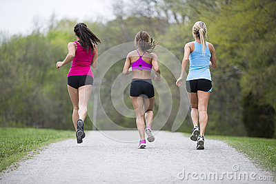Three beautiful woman run in the park