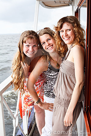 Three beautiful young females on deck of ship