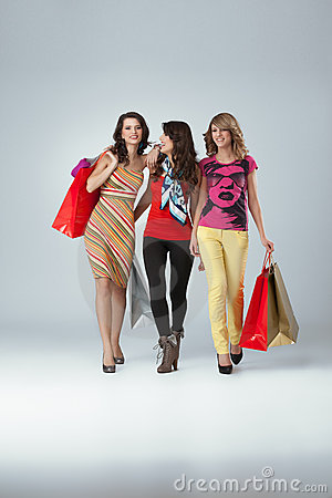 Three beautiful young women holding shopping bags