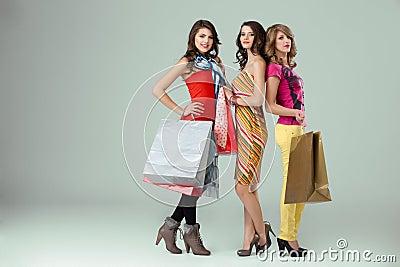 Three beautiful young women holding shopping bags