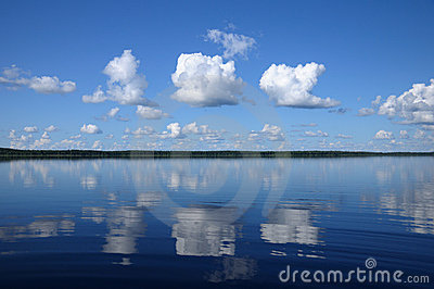 Three big clouds above the mirrored lake