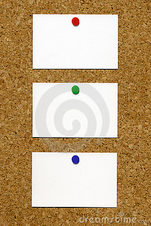 Three blank white business cards on a noticeboard.