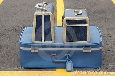 Three blue suitcases on yellow lines
