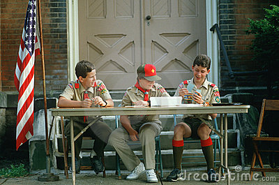 Three Boy Scouts seated at table Editorial Photography