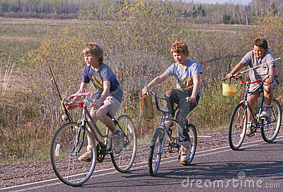 Three boys on bicycles with fishing poles Editorial Photography