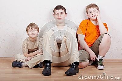 Three boys sit on floor with their legs tucked up