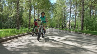 Three brothers riding bikes in sunny day. Children cycling in suburbs stock video