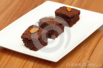 Three brownies with almonds on a white plate