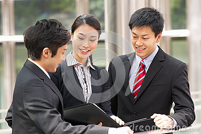 Three Business Colleagues Discussing Document