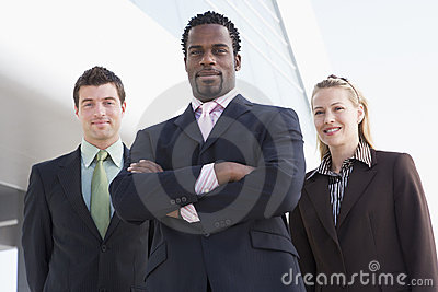 Three business people standing outdoors by buildin