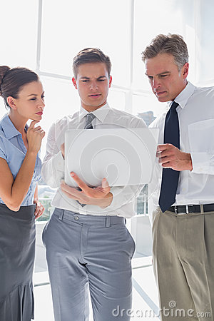 Three business people using a laptop