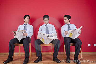 Three businessman reading a newspaper