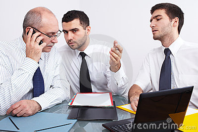 Three businessman sitting at table during meeting