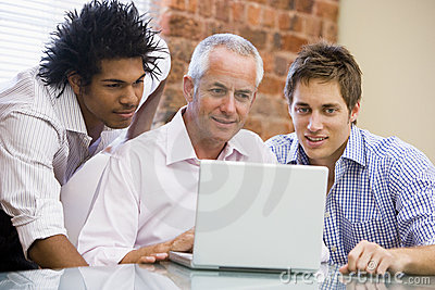 Three businessmen in office looking at laptop