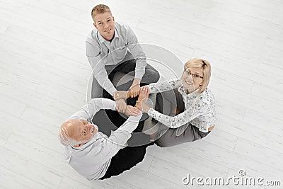 Three businesspeople meditating on floor