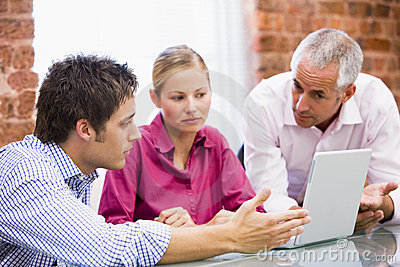 Three businesspeople in office with laptop