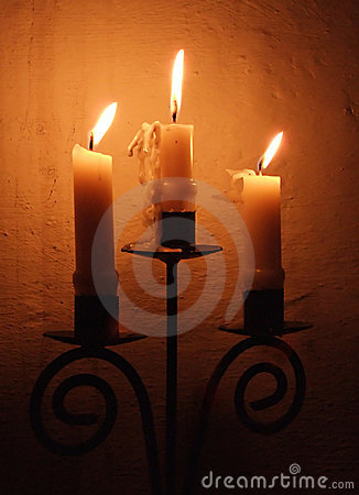 Three candles burning in a 13th century English parish Church