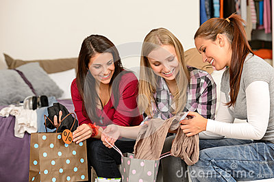 Three cheerful girls with clothes from sale