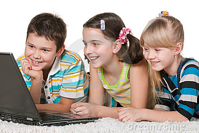 Three cheerful kids are using a laptop