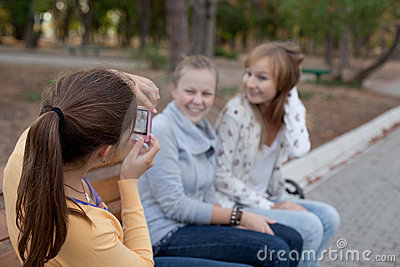 Three cheerful student girls making photos