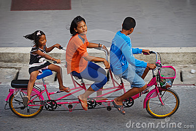 Three childred on tandem bicycle on a road Editorial Photo