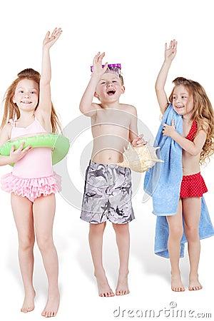 Three children in beach suits with beach accessories