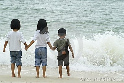 Three children playing with waves