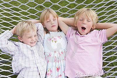 Three children relaxing and sleeping in hammock