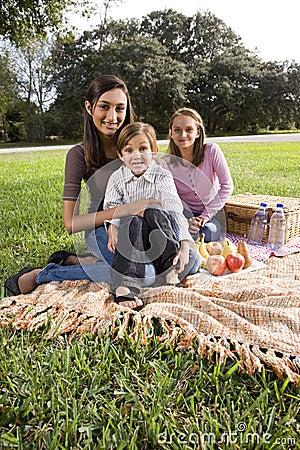 Three children sitting on picnic blanket in park