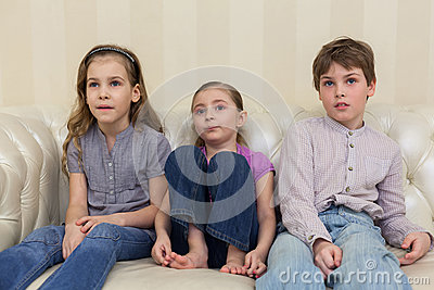 Three children sitting and watching TV