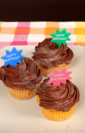 Three chocolate frosted cupcakes with