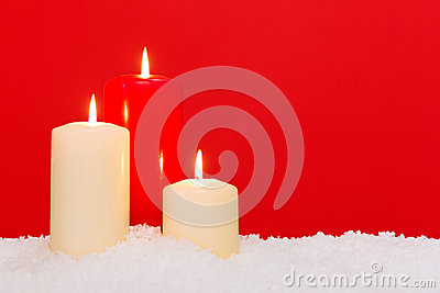 Three Christmas candles red background
