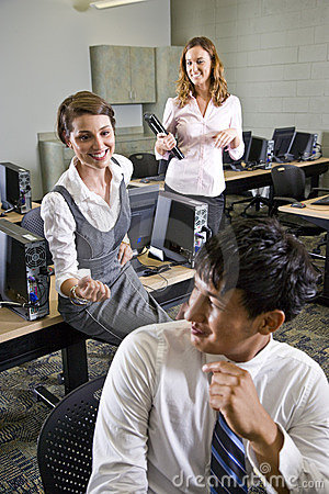 Three college students talking in computer lab